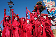 Spectacularly costumed Red Rebels lead a procession of Extinction Rebellion activists on 20th September 2019 in Penzance, United Kingdom. The Red Rebells performance activist troupe dedicated to illuminating the global environmental crisis and supporting groups and organisations fighting to save humanity and all species from mass extinction. Extinction Rebellion is a climate change group started in 2018 and has gained a huge following of people committed to peaceful protests. These protests are highlighting that the government is not doing enough to avoid catastrophic climate change and to demand the government take radical action to save the planet.