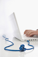 Woman using lap top with knotted cable in studio close up on knot