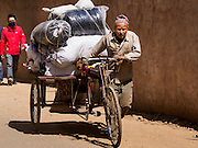 06 MARCH 2017 - KATHMANDU, NEPAL: A porter makes deliveries by bicycle in Kathmandu.      PHOTO BY JACK KURTZ