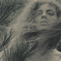 Head shot of female youth with long hair blowing the wind standing alone outdoors