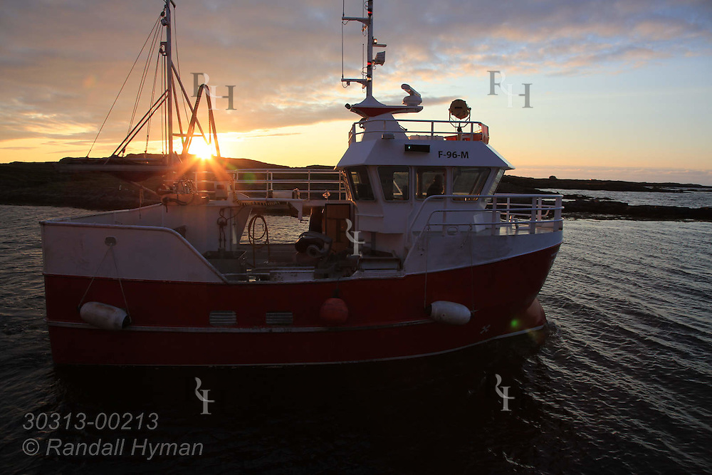 Fishing boat leaves dock at sunset on Ingoya island, Finnmark, Norway.