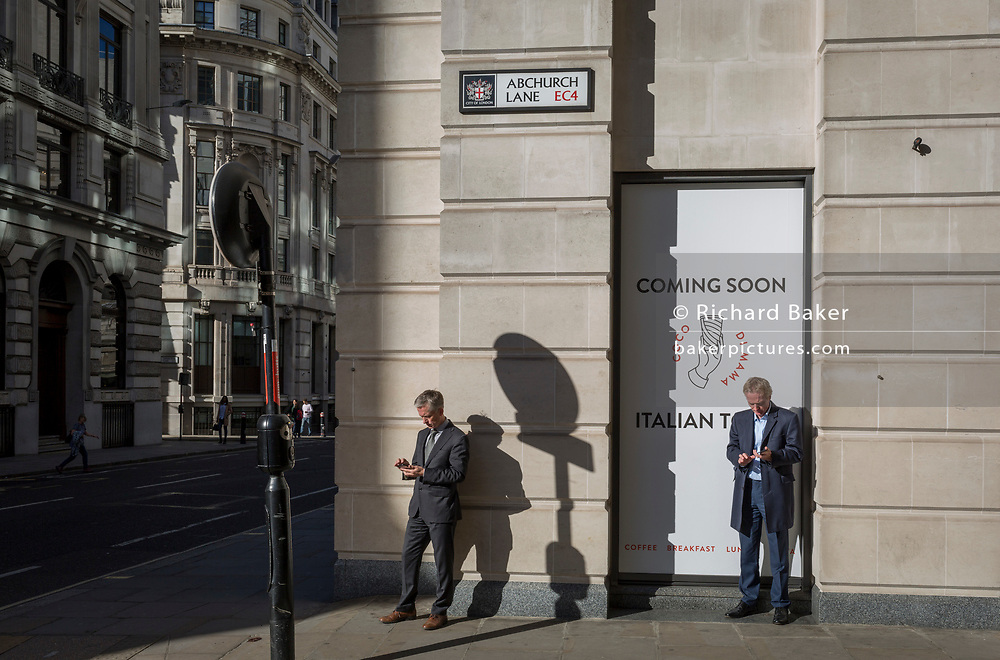 City businessmen check for messages and use social media on the corner of King William Street and Abchurch Lane EC4, on 27th October 2017, in the City of London, England.