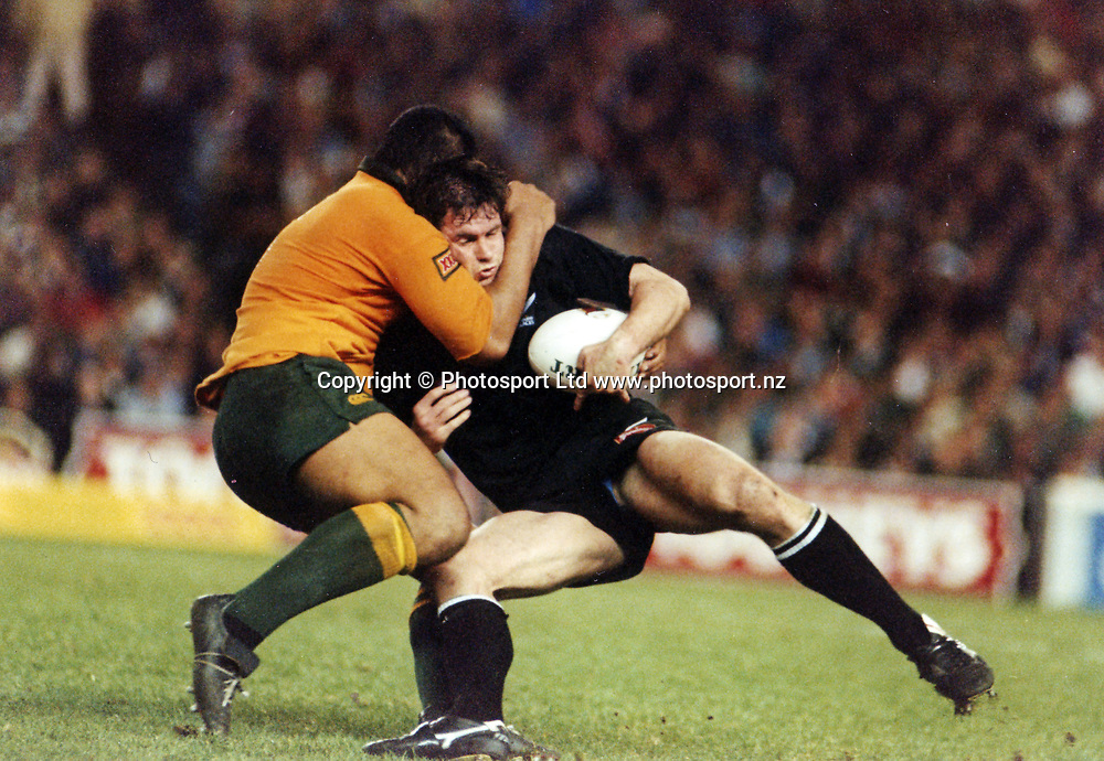 All Blacks flanker Mike Brewer is tackled during the international rugby union match between the All Blacks and Australia, year unknown. Photo: PHOTOSPORT<br /> <br /> <br /> nz new zealand black