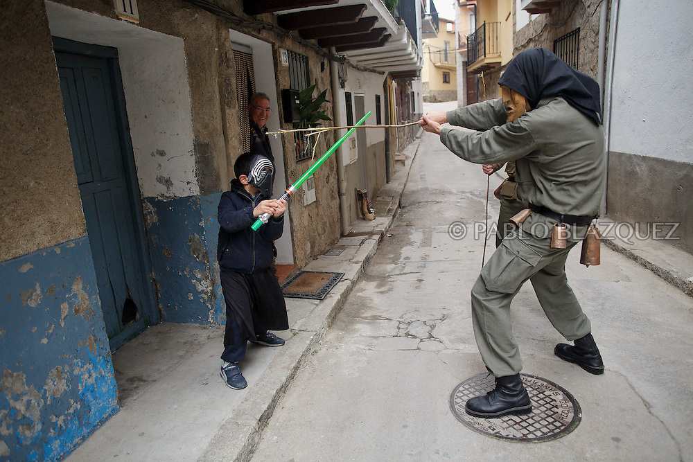 A Machurrero from Pedro Bernardo plays with swords with child dressed as Darth Vader in the street during Carnival on February 6, 2016 in Pedro Bernardo, in Avila province, Spain. The origins of this pagan festival are unknown. The Machurreros wear wood masks, a military dress, black handkerchief, cowbells, and hold wicker stick. The festival disappeared after Dictator Franco forbid carnival festivals in 1937, but it was recently recovered. Before disappearing, male villagers after the military service, used to dress as Machurreros as they run along the streets scaring children and adults with their wicker stick to bring fertility to the land and expel the evil spirits. (© Pablo Blazquez)