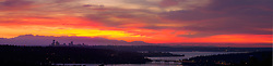 North America, USA, Washington, Seattle. Skyline viewed at sunset from Bellevue looking west. Olympic mountains in background, Lake Washington and Mercer Island in foreground.