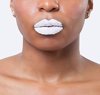 Close-up shot of young African American woman with white lips over white background