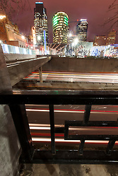 Vertical photo of urban interstate highway and traffic motion surrounding downtown Kansas City, Missouri's central business district area.