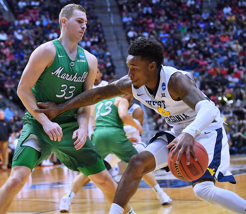 SAN DIEGO, CA - MARCH 18:  West Virginia Mountaineers guard Daxter Miles Jr. (4) drives against Marshall Thundering Herd guard Jon Elmore (33) during a second round game of the Men's NCAA Basketball Tournament at Viejas Arena in San Diego, California.  (Photo by Sam Wasson)