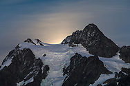 The moon rises behind Mount Shuksan. I photographed this from Artist Point in the Mount Baker-Snoqualmie National Forest in Washington State, USA.  Photographers were lined up in the Artist Point parking lot for this shot, but I stumbled into it as I had no idea it was a full moon.