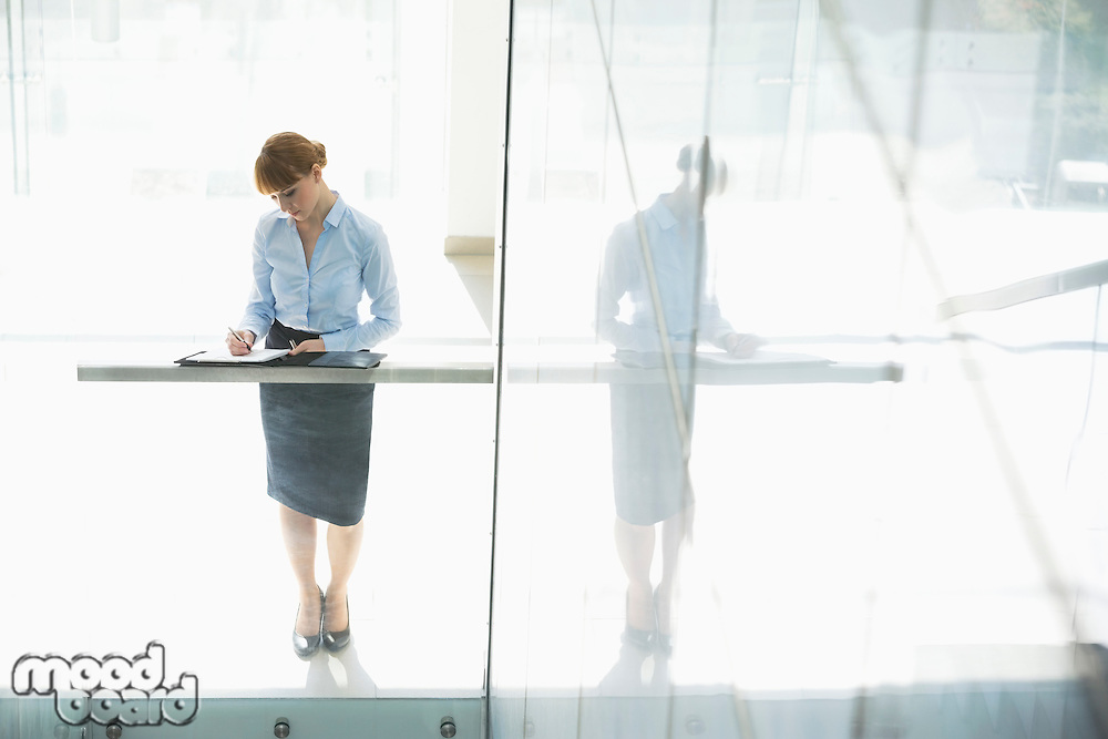 Full-length of businesswoman writing on document in office