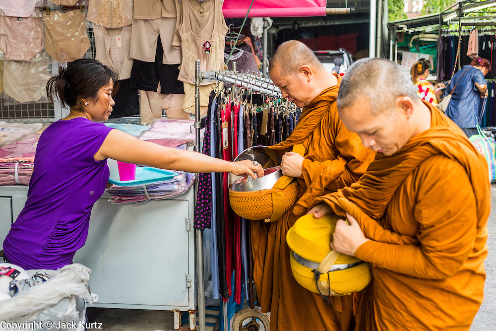 06 JUNE 2013 - BANGKOK, THAILAND:     A woman makes merit by giving food to Buddhist monks who stopped in her wholesale clothing shop on their morning alms rounds in Bobae Market in Bangkok. Bobae Market is a 30 year old market famous for fashion wholesale and is now very popular with exporters from around the world. Bobae Tower is next to the market and  advertises itself as having 1,300 stalls under one roof and claims to be the largest garment wholesale center in Thailand.       PHOTO BY JACK KURTZ
