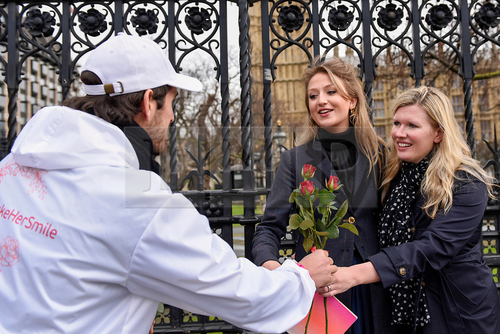 """© Licensed to London News Pictures. 08/03/2017. London, UK. Women receive roses.  A flashmob takes place in Parliament Square as part of International Women's Day.  Apparently backed by the Russian government, a giant balloon is unsuccessfully inflated bearing the text """"From Russia With Love"""" and """"#makehersmile"""" with organisers handing out roses to unsuspecting female passers by. Photo credit : Stephen Chung/LNP"""
