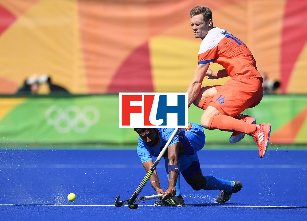 India's Surender Kumar hits the ball past Netherland's Mirco Pruijser during the men's field hockey Netherland's vs India match of the Rio 2016 Olympics Games at the Olympic Hockey Centre in Rio de Janeiro on August, 11 2016. / AFP / MANAN VATSYAYANA        (Photo credit should read MANAN VATSYAYANA/AFP/Getty Images)