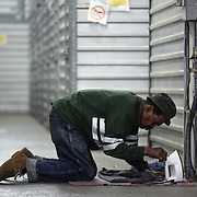 WASHINGTON, DC-OCT14: A homeless man (did not want to be identified) uses an electrical outlet to iron his clothes in a hallway between storage units at Capital Self-Storage, October 14, 2015, in Washington, DC. Many of the area homeless have possessions they want to keep safe, just nowhere permanent to live, so they store their belongings at Capital Self-Storage, where an upper-level unit costs $30/month. Some of the homeless patrons also spend their days in their storage units, when shelters are closed during midday hours. The storage facility near 3rd and Florida Avenue in Northeast, Washington, DC, is about to be replaced by a boutique hotel. (Photo by Evelyn Hockstein/For The Washington Post)