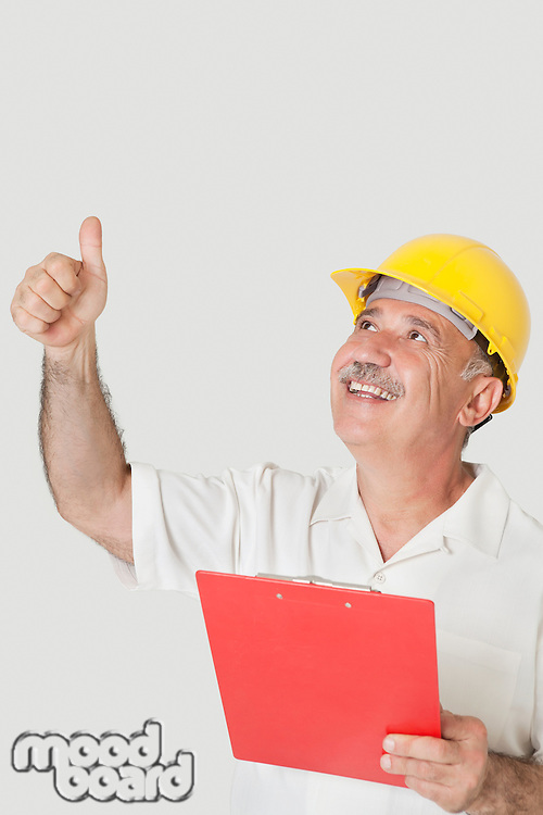 Happy senior constructor holding clipboard while gesturing thumbs up over gray background
