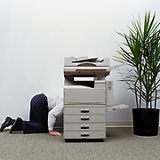 60's Businessman kneeling beside photocopier, side view