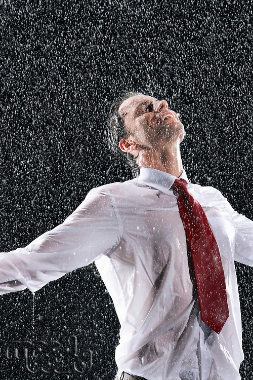 Businessman standing arms spread facing incoming rain