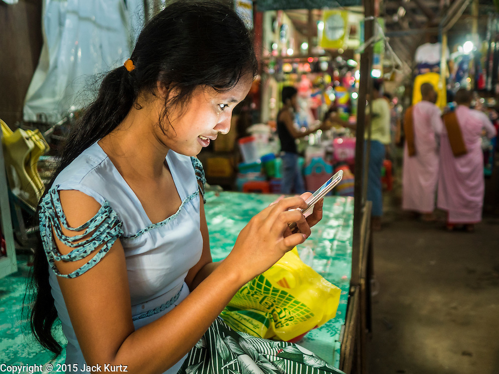 27 OCTOBER 2015 - YANGON, MYANMAR: A girl is illuminated by the glow from her smart phone in the market at Aungmingalar Jetty in Yangon. The market is home to one of the largest fish markets in Yangon and a meat and produce market.    PHOTO BY JACK KURTZ