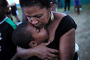 A woman consoles her son outside of the closed official funeral for Fidel.