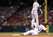ANAHEIM, CA - APRIL 15:  Jed Lowrie #8 of the Oakland Athletics leaps in the air while covering second base as Chris Iannetta #17 of the Los Angeles Angels of Anaheim steals safely during the game against the Los Angeles Angels of Anaheim at Angel Stadium on Tuesday, April 15, 2014 in Anaheim, California. The Athletics won the game 10-9 in eleven innings. (Photo by Paul Spinelli/MLB Photos via Getty Images) *** Local Caption *** Jed Lowrie;Chris Iannetta