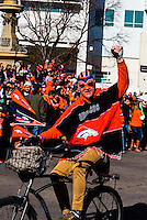 Fan on a bicycle at the Denver Broncos Super Bowl 50 Victory Parade, Downtown Denver, Colorado USA.