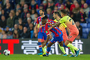 Manchester City defender João Cancelo (27) pushes Crystal Palace forward Wilfried Zaha (11) during the Premier League match between Crystal Palace and Manchester City at Selhurst Park, London, England on 19 October 2019.