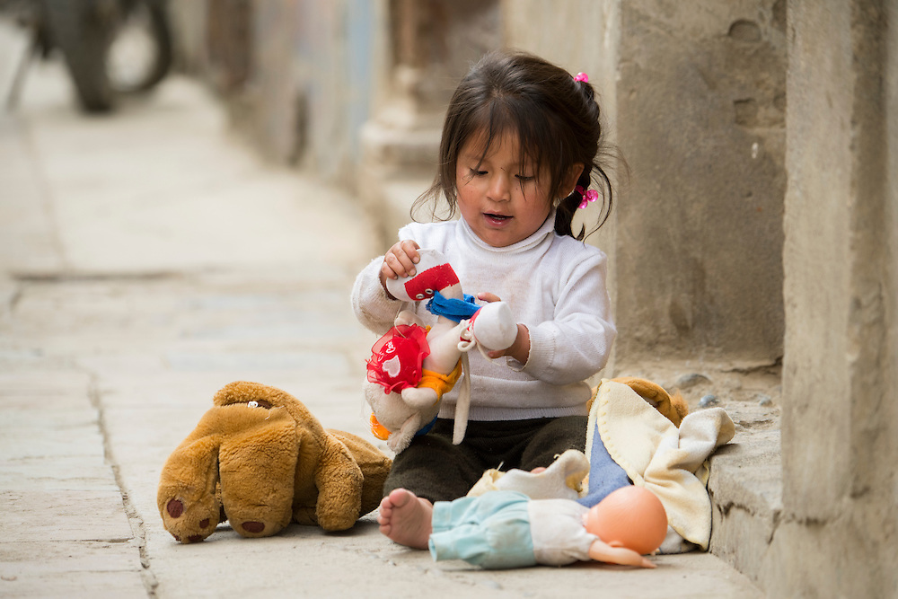 South America,Peru, little girl playing with toys in Ajanaco near Manu National Park