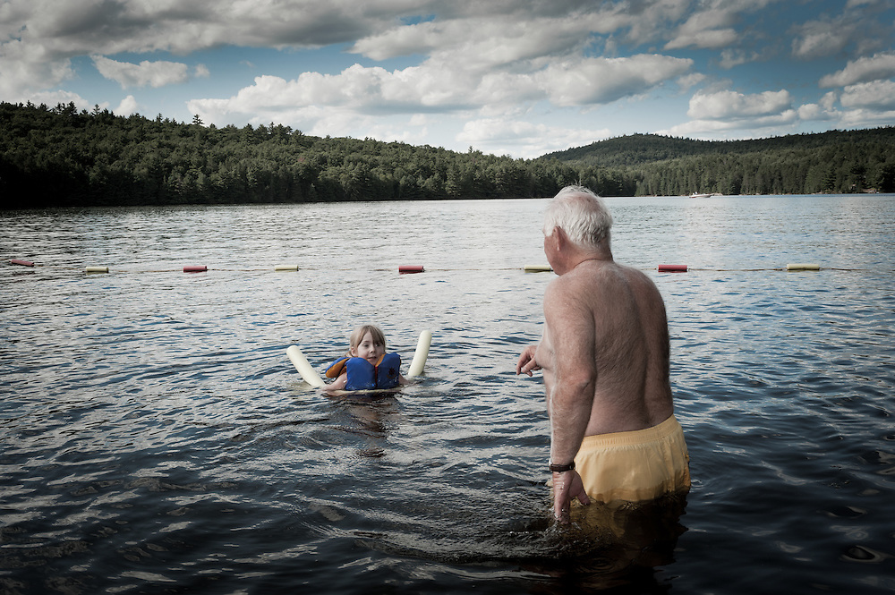 Grandfather teaching granddaughter to swim at the lake.
