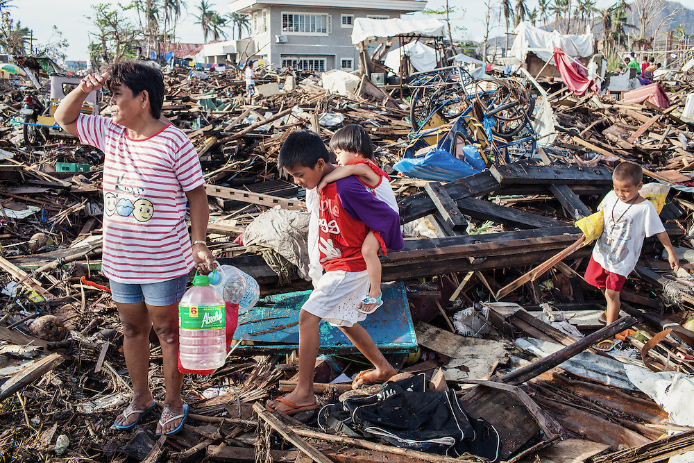 A family finds their way walking on top of debris from broken homes and items destroyed by Typhoon Haiyan.