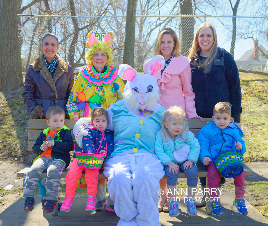 North Merrick, New York, USA. March 31, 2018. Back Row, L-R, Hempstead Town Clerk SYLVIA CABANA; BETTY TUCKER (clown) a member of American Legion Auxiliary Unit 1282; Hempstead Town Supervisor LAURA GILLEN; and SUE MOLLER, Co-President of North and Central Merrick Civic Association; pose with Easter Bunny sitting with young boys and girls at the Annual Eggstravaganza, with Easter Egg Hunt, held at Fraser Park and hosted by North and Central Merrick Civic Association (NCMCA) and American Legion Auxiliary.