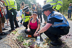 © London News Pictures. 27/07/2013. Balcombe, UK.  Police talk to a demonstrator who as she refuses to move from the road. Anti Fracking activists and local villagers attempt to blockade a drilling site in Balcombe, West Sussex which has been earmarked for fracking. A number of demonstrators at the site have been arrested. Photo credit: Ben Cawthra/LNP