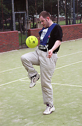 Man with learning disability playing with football on artificial pitch,