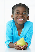 Girl (5-6) holding pear and smiling portrait