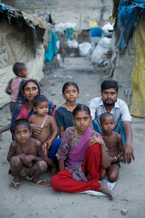 Sahera with her family outside their home. LtoR:<br />Brother Shabikur, age 6<br />Mother Zohra, age 35<br />Sister Shahida, age 2<br />Sister Salina, age 8<br />Sahera, age 10<br />Father Sameer, age 40<br />Sister Shazda, age 4<br /><br />Sahera's sister and brother Sameeran and Muslim not photographed.<br /><br />The rag-picking community of Shanti Busti (literally &quot;Peace Slum&quot;) which comprises 210 households have been living and working in Lucknow for the past twenty years. Originally from Assam, their language and culture differs from the wider population of Lucknow who speak Hindi. The low status of the rag-pickers' work together with their minority status as Muslims speaking Assamese makes them particularly vulnerable to stigma and discrimination. The rag-pickers also suffer insecurity of tenure over the land upon which Shanti Busti is built. Families pay a rent of INR100-150 (GB&pound;1.25-GB&pound;1.90) to a &quot;landlord&quot; who provides then some protection from eviction by the government. The community's status is further undermined by the fact that many in wider society falsely charge them with being illegal immigrants from Bangladesh. This effectively denies the rag-pickers claim to any of the rights and services afforded to other Indians including the right to vote. Without political representation the people of Shanti Busti rely on the work of Oxfam and its partners for the provision of basic services. <br /><br />Sahera Khatoon is ten years old. She lives with her two parents and five of her six siblings in a small shack built of discarded plastic sacking and bamboo poles. Sahera's father Sameer and mother Zohra arrived from Barpeta district in Assam 21 years ago. They and their families were poor landless labourers suffering the financial insecurity that comes with irregular work. Like many of their neighbours in Barpeta district, they were encouraged to make the journey to Lucknow by a refuge contractor who promised a regular income i