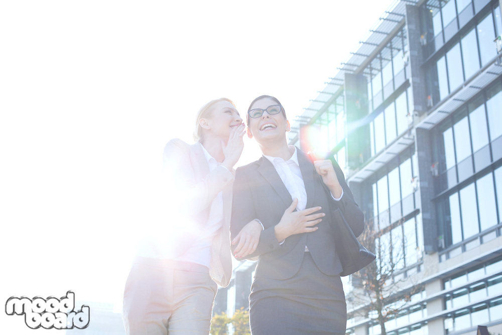 Happy businesswoman whispering in colleague's ear outside office building on sunny day