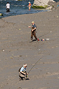 Fisherman wade through thick mud to snag fish for silver salmon in summer along Potter Creek in the Chugach State Park outside Anchorage, Alaska.