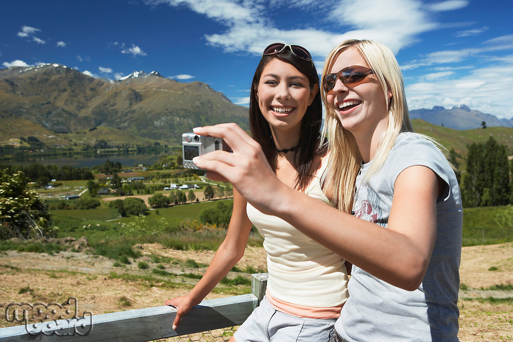 Two women taking picture against fence with mountains behind