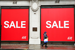 "© Licensed to London News Pictures. 23/12/2018. London, UK. A woman walking past a H&M store with a window displaying ""SALE"". Last minute Christmas shoppers take advantage of pre-Christmas bargains in London's Oxford Street. Fewer shoppers have been reported shopping in Britain's high streets as online sales increase. Photo credit: Dinendra Haria/LNP"