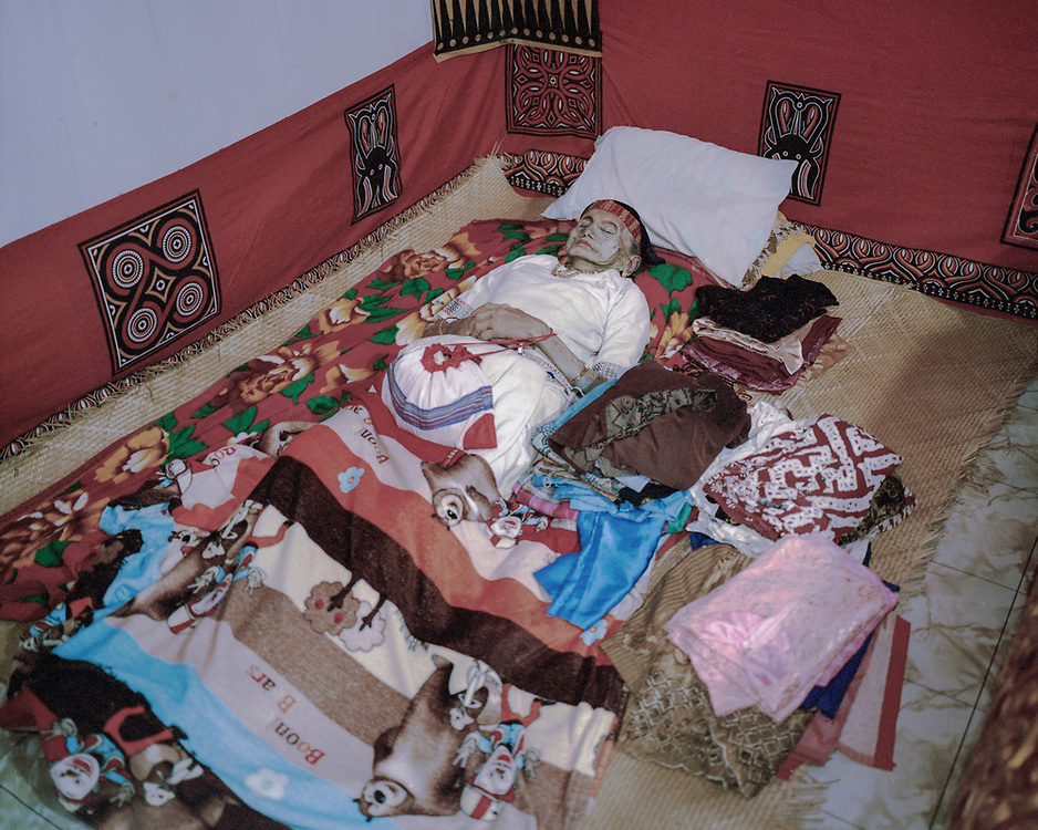 In Torajan culture, death is not necessarily the end.  The body of Lai' Tiku who passed on a few months ago is seen in her home surrounded by her personal belongings which will be placed inside her coffin.  The matriarch in her family, Nenek Lai' Tiku passed away at age 102, she is survived by 10 children, 49 grandchildren, and 162 great-grandchildren.