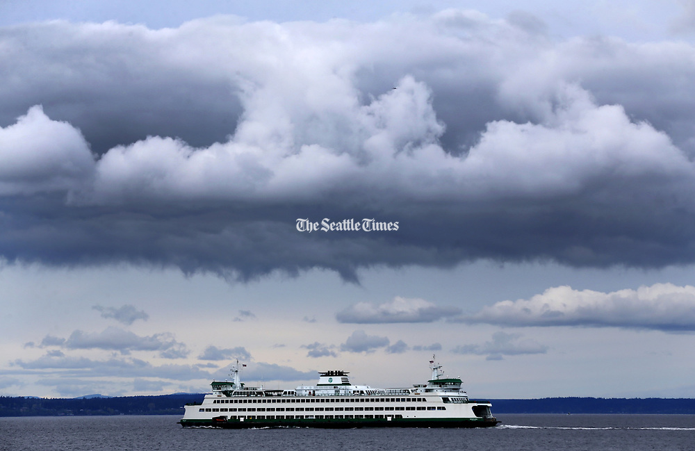Spectacular storm-cloud formations hover over a Washington State Ferry in Elliott Bay in this view from West Seattle. (Ken Lambert/The Seattle Times)