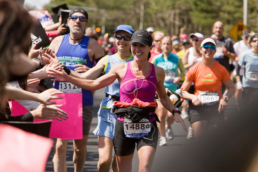 runners slapping hands with spectators as they pass Wellesley College
