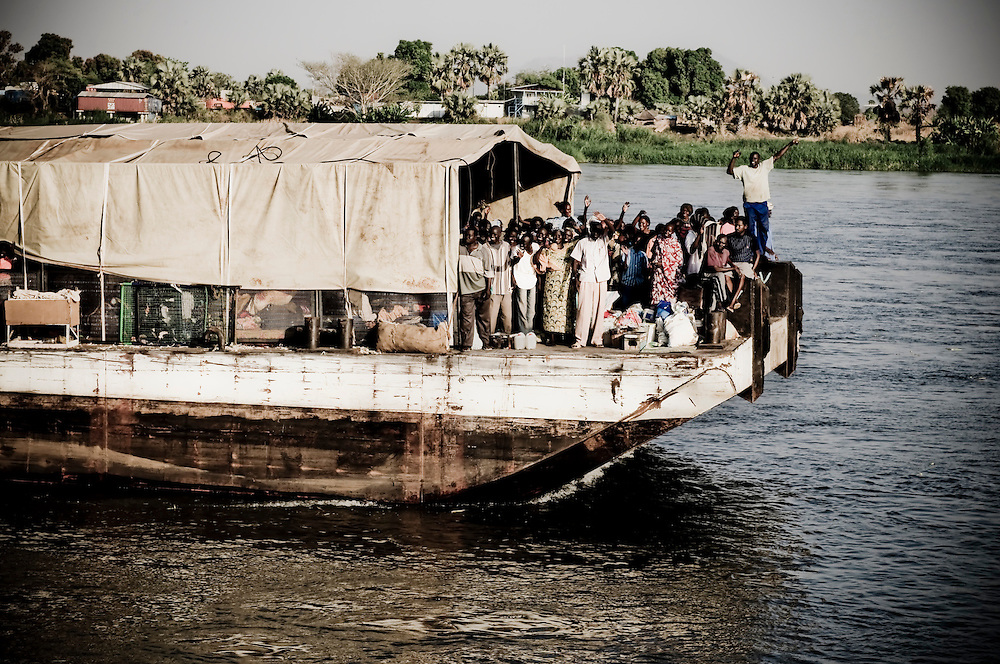 Southern Sudanese arrive home in a barge along the Nile River to Juba from Khartoum in a 27 day journey that saw them arrive one day before Sudan's anticipated referendum. The Southerners returned home from the North for fear of retribution should the South declare  independence. Southern Sudan will vote on January 9 to decide whether or not to remain as part of Sudan or set off alone as the world's newest country. (© William B. Plowman)