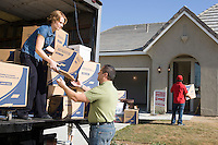 Man and woman unloading truck of cardboard boxes