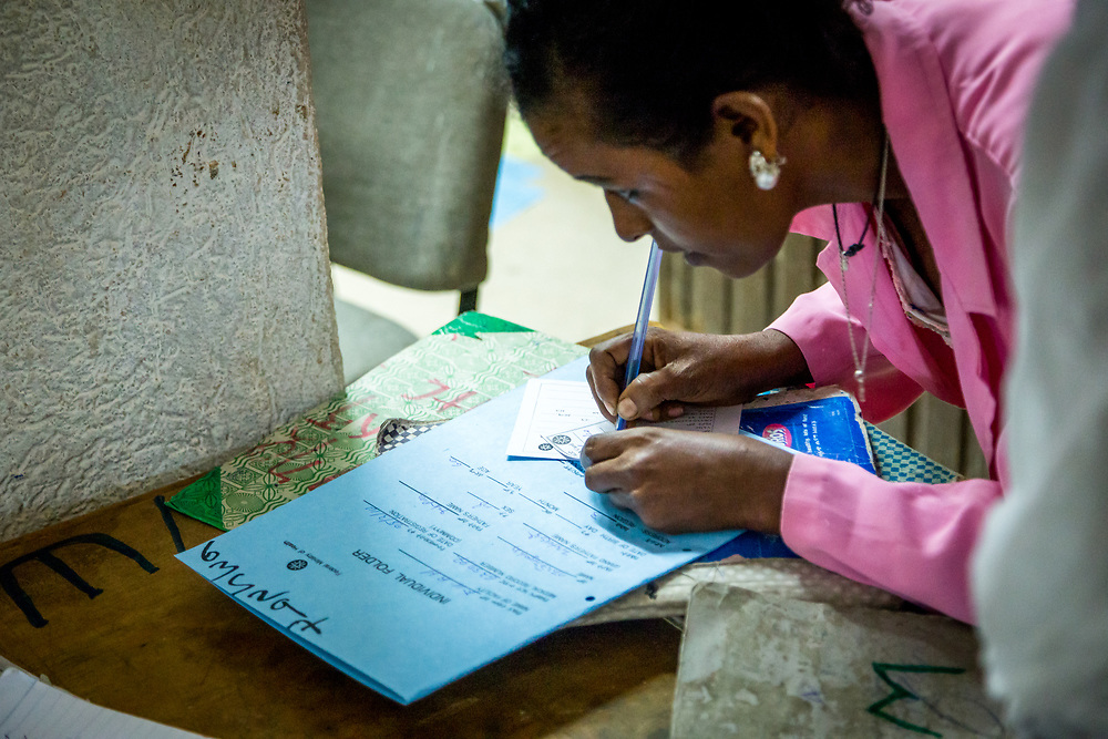 INDIVIDUAL(S) PHOTOGRAPHED: N/A. LOCATION: Felege Hiwot Referral Hospital, Bahir Dar, Ethiopia. CAPTION: A hospital staffer quickly jots down information on a newly admitted patient's folder.