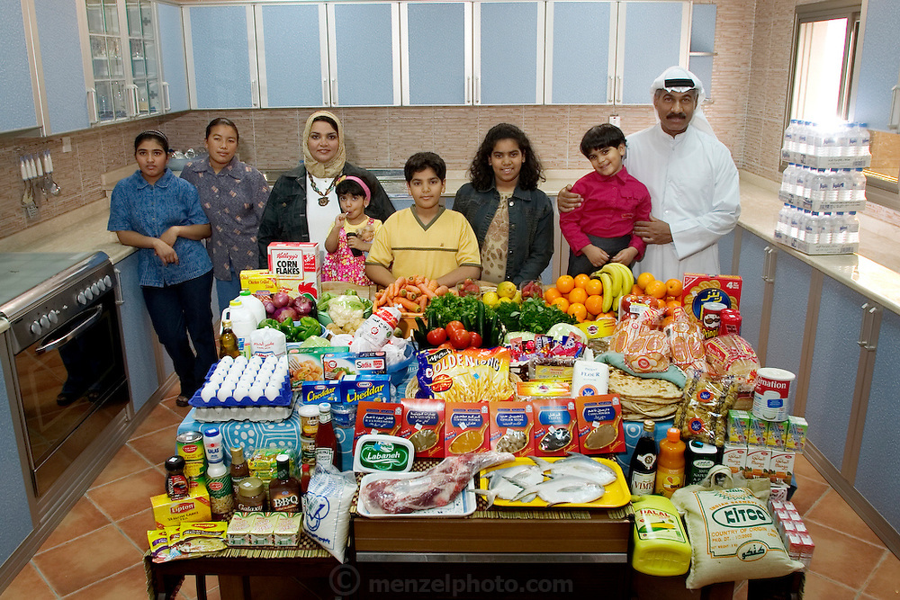 (MODEL RELEASED IMAGE). The Al Haggan family and their two Nepali servants in the kitchen of their home in Kuwait City, Kuwait, with one week's worth of food. Hungry Planet: What the World Eats (p. 196).