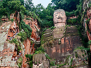 China, Sichuan. The Leshan Grand Buddha at the confluence of Min Jiang and Dadu River, seen from an excursion boat.