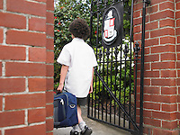 Elementary schoolboy walking through school gate back view