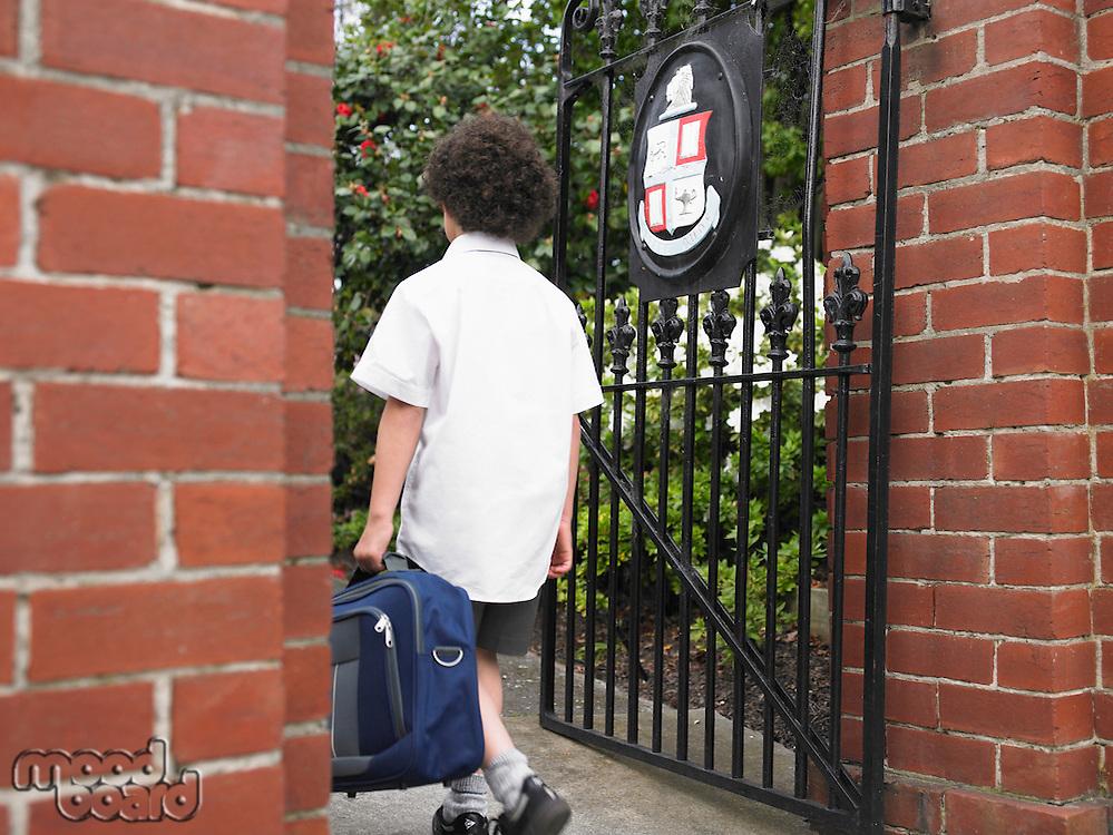 Elementary schoolboy walking through school gate back view