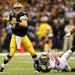November 6, 2011; New Orleans, LA, USA; New Orleans Saints quarterback Drew Brees (9) throws as Tampa Bay Buccaneers safety Tanard Jackson (36) grabs his leg during the first quarter of a game at the Mercedes-Benz Superdome. Mandatory Credit: Derick E. Hingle-US PRESSWIRE