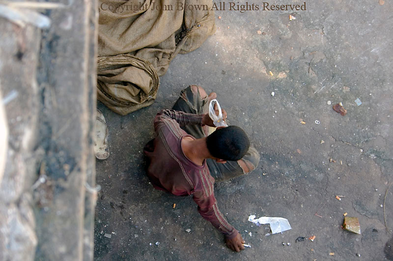 A scavenger man living in poverty sits on a sidewalk while he sniffs glue & smokes a cigarette in Kampong Cham, Cambodia.